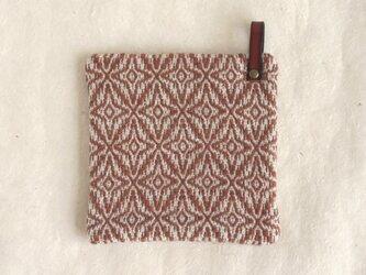 レンガ色模様手織りのポットマットの画像