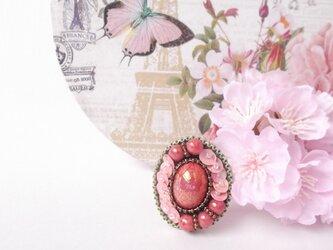 コーラルピンクの桜色に染まるブローチの画像