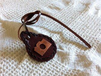 銅板のカメラの形を革にあしらったチャームの画像