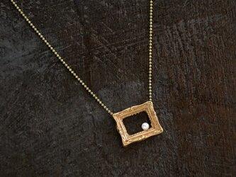 額縁とパールのネックレスの画像