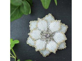白いビーズで編んだ花のブローチの画像
