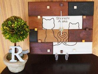アンティークな木の時計・寄り添う猫の画像