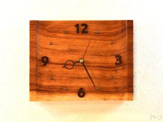 日の出前の朝焼けのパノラマのような木の時計の画像