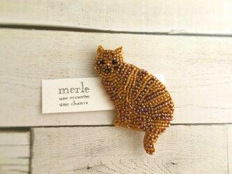 座る茶トラ猫のブローチの画像