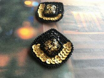 水面に浮かぶ金とスパンコールのマロン形ブローチの画像