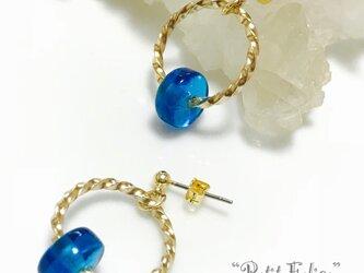 キラリと輝くツイストフープにブルーのガラスビーズを添えたピアス ポストタイプの画像