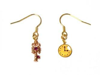 小さなピンク・ゴールドの鍵と懐中時計の金色ピアスの画像