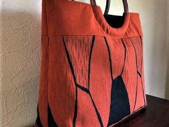 オレンジ色幾何学模様の名古屋帯の手提げ 丸い木の手の画像
