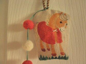 赤いマントの小さな馬のかざりの画像
