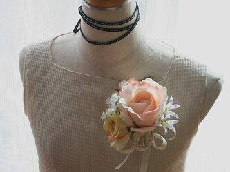 親しみを感じさせるクリームブラウンのバラのコサージュの画像