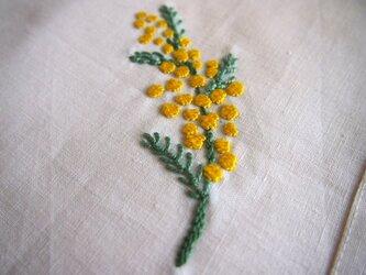 ミモザの一枝を刺したリネンのテーブルナプキンの画像