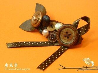 リボンとボタンのブローチ茶の画像