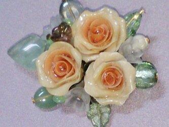 オレンジ色のバラのブローチの画像