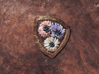 ポケットに花の刺繍ブローチの画像