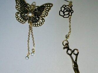 ハサミと蝶とバラのピアスの画像