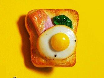 リアルな目玉焼きとベーコン載せパンの画像