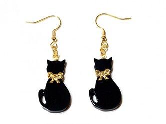 小さな金色リボン首輪の黒猫が揺れるゴールド・ピアスの画像