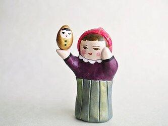 金の人形をかかげるひとの画像
