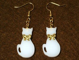 小さな金色リボン首輪の白猫が揺れるゴールド・ピアスの画像