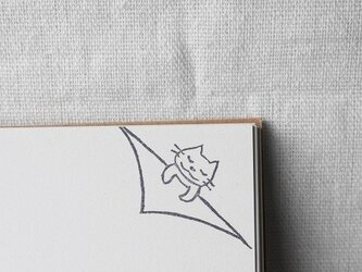 ノートの隅でネコさんが眠るはんこ(受注制作)の画像