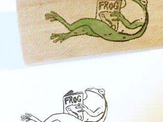 脚を組んで本を読むカエルはんこの画像