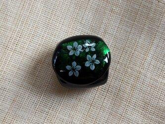 白い小花の帯留(緑)の画像