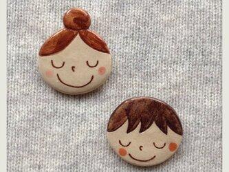 陶の女の子・男の子のブローチの画像