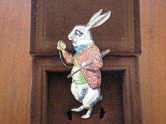 時計を見つめるウサギのブローチの画像