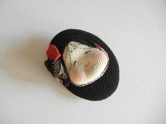 おかめのレリーフ風ブローチ(黒×赤)の画像
