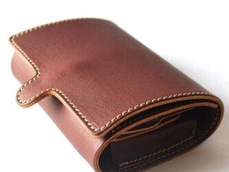 くるむように包まれた3つ折りレザー財布。の画像