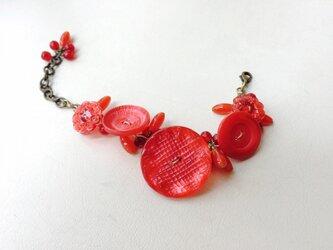 赤いボタンのブレスレットの画像