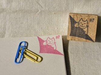 ネコさんがノートの隅で挨拶するはんこの画像