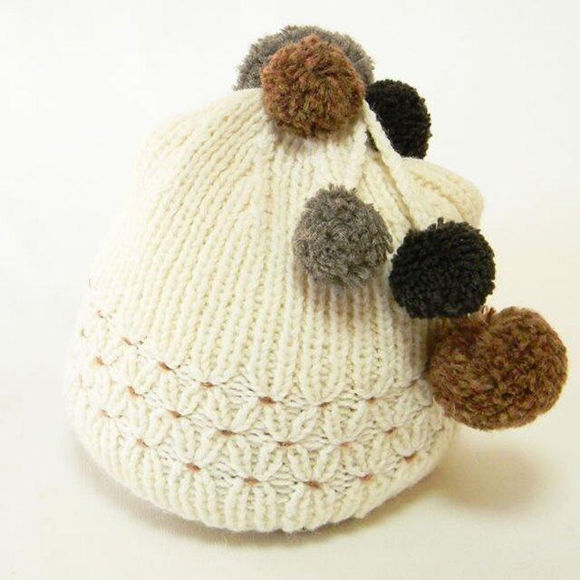 揺れるポンポンとスモッキングがポイントの手編みのニット帽。 可愛さもありながら懐かしい雰囲気【PL1200-OfWhite】の画像1枚目