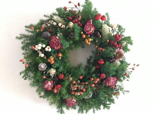 赤い実と赤いバラのクリスマスリースの画像1枚目